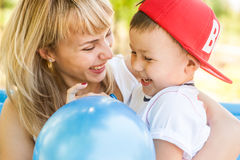 Mother and son playing. Together outdoors in park with soap bubbles Stock Images