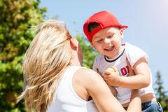 Mother and son playing. Together outdoors in park with soap bubbles Stock Image