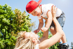 Mother and son playing. Together outdoors in park with soap bubbles Stock Photos