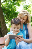 Mother and son playing together on tablet Royalty Free Stock Photography