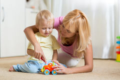 Mother and son playing with toy cars indoors Royalty Free Stock Photo