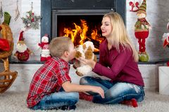 Merry Christmas and Happy Holidays!.Mother and son playing with a toy dog by the fireplace. stock images