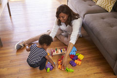 Mother And Son Playing With Toys On Floor At Home Royalty Free Stock Image