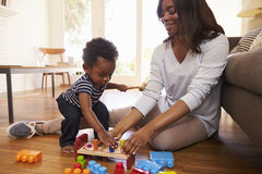 Mother And Son Playing With Toys On Floor At Home Stock Photography