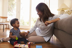 Mother And Son Playing With Toys On Floor At Home royalty free stock images