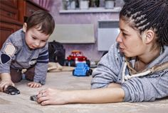 Black mother, little son, play with cars, happy family, non-stand. Mother And Son Playing With Toys On Floor At Home Royalty Free Stock Image