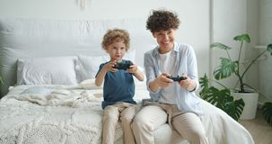 Mother and son playing video game sitting on bed in bedroom at home having fun. Mother and son are playing video game sitting on bed in bedroom at home having stock video footage