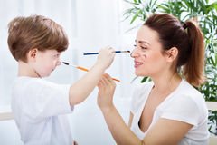 Mother and son playing with watercolors and brushes Royalty Free Stock Images