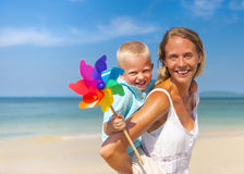 Mother and son playing with windmill on the beach Stock Photography