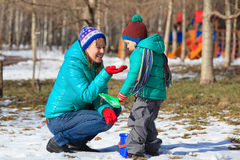 Mother and son playing in winter snow Stock Image