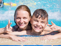 Mother and son in pool. Smiling beautiful women and her cute child - teen boy - in the pool. Mother learning to swim her son. Portrait of a happy family relax Royalty Free Stock Images