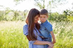Mother and son portrait against green trees family royalty free stock image