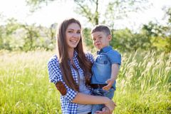 Mother and son portrait against green trees family stock photo