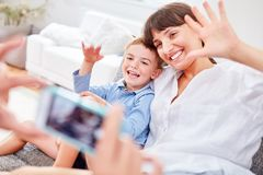 Mother and son pose for snapshot. Mother and son pose for a snapshot with the smartphone camera Royalty Free Stock Image