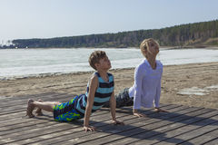 Mother and son practicing yoga on the beach Royalty Free Stock Photography