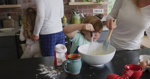 Mother and son preparing cookie on worktop in kitchen at home 4k. Front view of Caucasian mother and son preparing cookie on worktop in kitchen at home. They are stock video