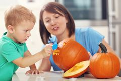 Mother and son preparing jack-o-lantern for Halloween. Picture of mother and son preparing jack-o-lantern for Halloween Royalty Free Stock Photography