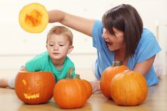 Mother and son preparing jack-o-lantern for Halloween. Picture of mother and son preparing jack-o-lantern for Halloween Royalty Free Stock Images