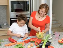 Mother and son preparing lunch and smiles. Son cuts red pepper stock photography