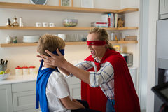 Mother and son pretending to be superhero in the kitchen. At home Stock Photo