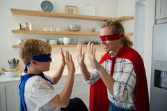 Mother and son pretending to be superhero in the kitchen. At home Royalty Free Stock Photography