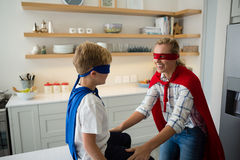 Mother and son pretending to be superhero in the kitchen. At home Royalty Free Stock Photos