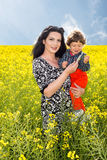Mother and son in rapeseed field Stock Photos