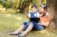 Mother and son read a book together Stock Photo