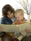Mother and son reading. A book on a chair royalty free stock image