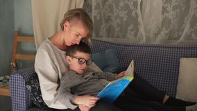 Mother and son reading a book stock video footage