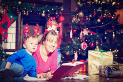 Mother and son reading book by fireplace on royalty free stock image