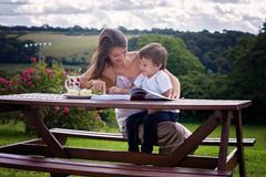 Mother and son, reading a book outdoor, summer day Stock Photography