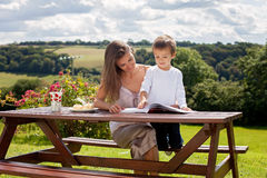 Mother and son, reading a book outdoor, summer day Royalty Free Stock Photo
