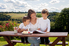 Mother and son, reading a book outdoor, summer day Royalty Free Stock Image