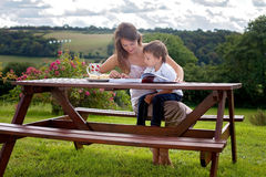 Mother and son, reading a book outdoor, summer day Stock Image