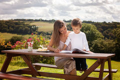 Mother and son, reading a book outdoor, summer day Stock Photo