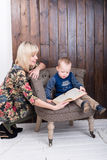 Mother and son reading a book. Sitting on a chair Royalty Free Stock Photo