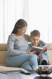 Mother and son reading book on sofa at home stock photos