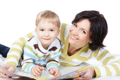 Mother and son reading book together over white Royalty Free Stock Photos