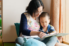 Mother and son reading. Chinese mother and son reading by window Stock Photo