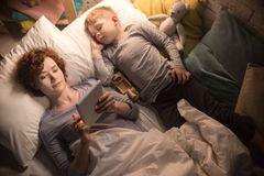 Mother and Son Reading Stories in Bed. Directly above portrait of mother and son reading book together from tablet lying in bed before sleep, enjoying stories in Stock Photo