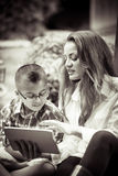 Mother and son reading from a touch pad black and white sepia to. Mother and son together on Mother's day reading from a touch pad black and white image Royalty Free Stock Image