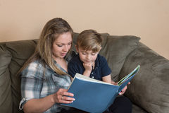 Mother and son reading. A young boy listens attentively as his mother reads to him royalty free stock photography