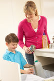 Mother And Son Recyling Waste At Home Stock Images