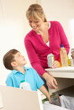 Mother And Son Recyling Waste At Home Royalty Free Stock Photos