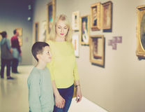 Mother and son regarding paintings in halls of museum Royalty Free Stock Images