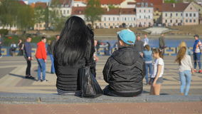 Mother with son relax in the city and watch sport games - slowmo 180 fps stock video