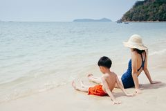 A mother and son relax and sitting  on the beach and sea outdoors at Blue sky stock photos