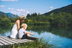 Mother and son relaxing on nature. Zelenci lake, Slovenia, Europe. Mother and son on wooden bridge on nature background of lake and mountains. Travel, Family stock images
