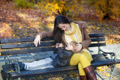 Mother and son relaxing on park bench. Happy mother and son enjoying in park in autumn. Little boy is lying down in mother's lap and talking to her Stock Photo